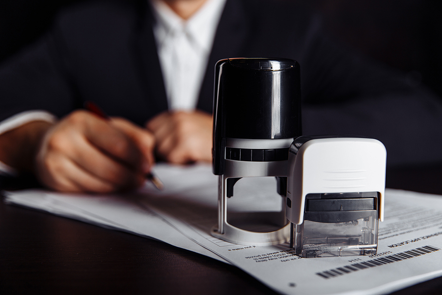 Businessman using adjustable date stamps on documents